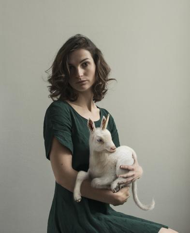 Autoportrait de Laure Fauvel tenant dans ses bras une jeune licorne.