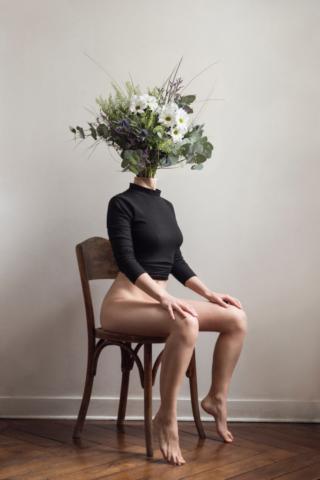 Corps de femme assis sur une chaise, un bouquet de fleur sort de son cou à la place de sa tête comme si elle n'était qu'un vase